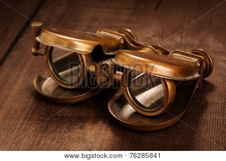 Vintage opera glasses binoculars on old wooden background