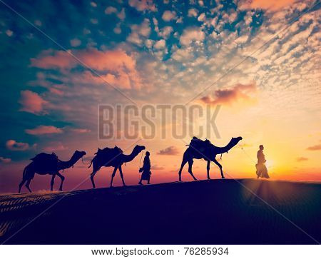 Vintage retro effect filtered hipster style image of  Rajasthan travel background - two indian cameleers with camels silhouettes in Thar desert dunes on sunset. Jaisalmer, Rajasthan, India