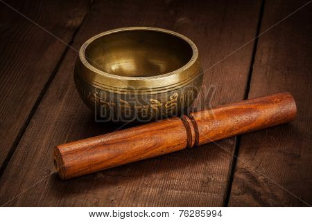 Tibetan buddhist singing bowl, rin gong, Himalayan bowl or suzu gong for  meditation, music, relaxation, and personal well-being with mallet on wooden background