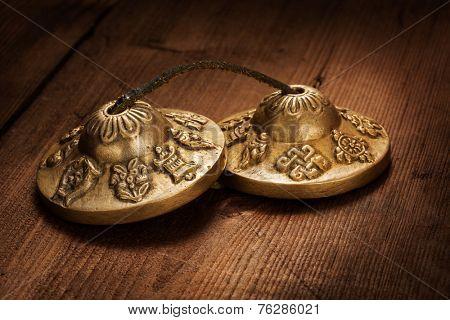 Tibetan Buddhist tingsha cymbals on wooden background