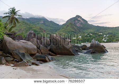 View across a rocky outcrop and calm ocean of Morne Seychellois, the highest mountain peak on Mahe, Seychelles, from Anse Trusalo beach