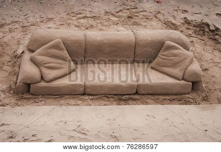 Sand sculpture of a sofa and cushions carved out of golden beach sand on the south bank of the River Tames, London, England