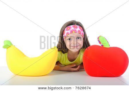 Niña en la mesa con un plátano grande y manzana