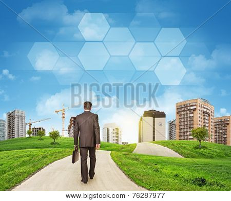 Businessman walks on road. Rear view. Buildings, grass field and sky with hexagons