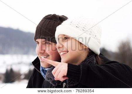 man showing girl the wonderful winter landscape by pointing with finger