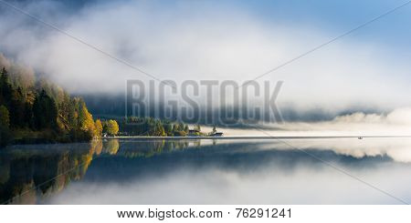 idyllic fall mood at tyrol lake with morning dust and colored forest