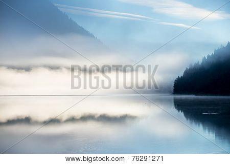 mountain alps lake at fall with mirroring dust abd blue sky