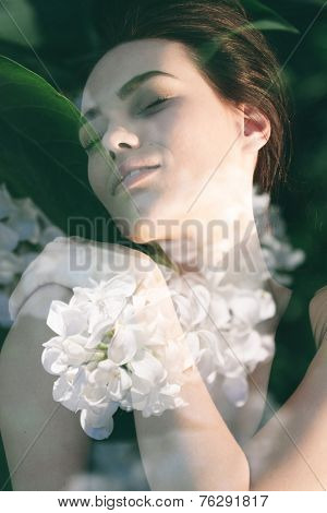 Double exposure portrait of gorgeous lady combined with photograph if lilac flowers in a tender composition