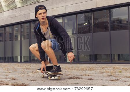 Young Blonde Guy On Skateboard In Casual Outfit In The Urban City Outdoors. Active. Sport. Copy Spac