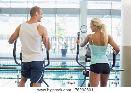 Rear view of a fit young couple working on x-trainers at the gym
