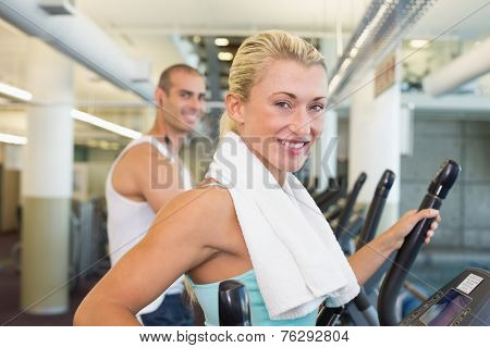 Side view portrait of a fit young couple working on x-trainers at the gym