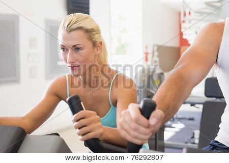 Close up of a fit young couple working on exercise bikes at the gym