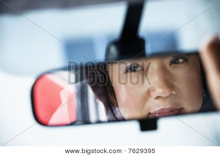 Woman Looking in Rearview Mirror