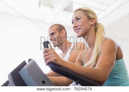 Low angle view of a fit young couple working on exercise bikes at the gym