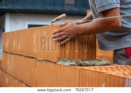anonymous construction worker on a building site when building a house built a wall of bricks. brick wall of a solid house. icon image for undeclared work and bungling