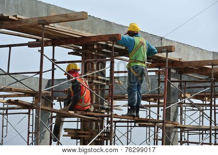 Construction workers dismantling beam formwork