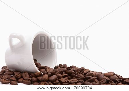 Cup with spilt coffee beans isolated on white