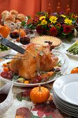 image of kumquat  - Carving roasted turkey on a server tray garnished with fresh figs grape kumquat and herbs on fall harvest table - JPG