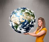 stock photo of cartographer  - Pretty young girl holding 3d planet earth - JPG