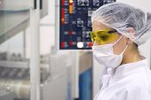 foto of pharmaceutical  - A female technician using the control panel of pill packaging machine.