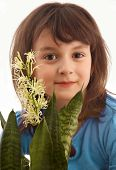 foto of sansevieria  - Smiling little girl with blooming home plant Sansevieria - JPG
