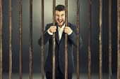 foto of delinquency  - angry screaming businessman behind the prison cell over dark background - JPG