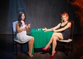 stock photo of hells angels  - Angel and devil playing cards at room - JPG