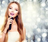 stock photo of singer  - Beauty model girl singer with a microphone singing and dancing over holiday glowing background - JPG