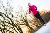image of cold-weather  - Young woman running outdoors on a cold winter day - JPG