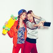 stock photo of selfie  - Two young girl friends standing having fun together - JPG