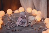 pic of wooden horse  - on wooden table lit garland, coffee cup, a wooden horse and bear