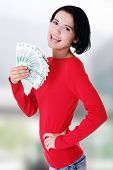 image of zloty  - Cheerful young lady holding cash  - JPG