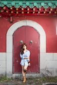 foto of filipina  - Asian woman in front of traditional Chinese door with ornate lion head knockers - JPG