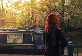 picture of houseboats  - A woman is standing by the canal next to a houseboat - JPG
