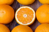 pic of orange  - many whole fresh oranges with one half of orange in center on wooden background - JPG