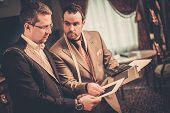 stock photo of tailoring  - Tailor and client choosing cloth and buttons for custom made suit  - JPG