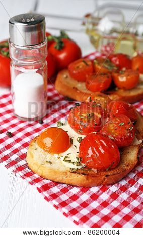Slices of white toasted bread with butter and canned tomatoes on wooden table, closeup