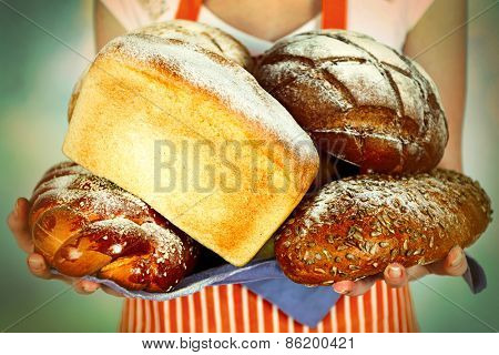 Armful of freshly bread in female hands on light blurred background