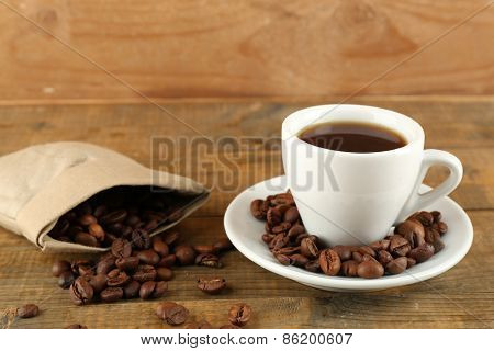 Cup of coffee with beans on rustic wooden background