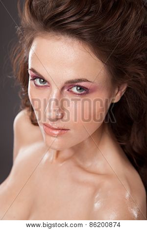 Fashion portrait of fresh young girl with shiny skin coated with oil.