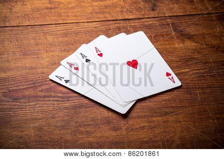 A group of four playing card aces on a stained oak wooden table.