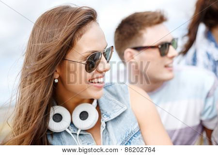 summer holidays, people and happiness concept - smiling teenage girl in sunglasses outdoors with friends