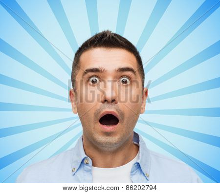 fear, emotions, horror and people concept - face of scared man shouting blue burst rays background