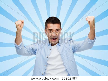 happiness, gesture, emotions and people concept - happy laughing man with raised hands blue burst rays background