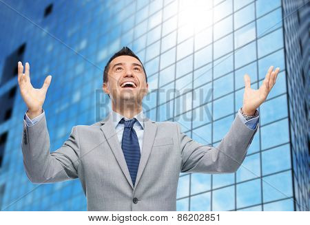 business, people and happiness concept - happy businessman in suit with raised hands laughing and looking up over office building background