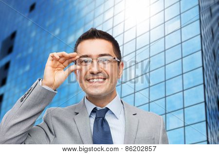 business, people, vision and office concept - happy smiling businessman in eyeglasses and suit over office building background