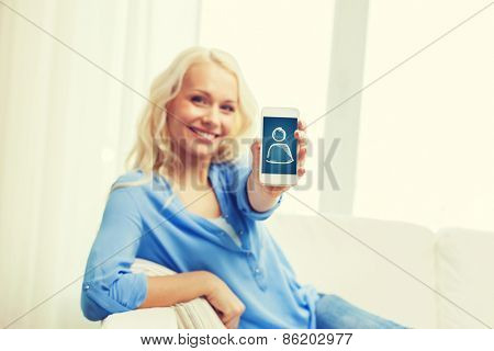home, technology and people concept - smiling woman with showing smartphone screen sitting on couch at home