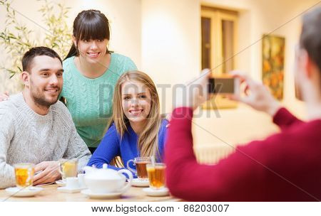 people, leisure, friendship and technology concept - group of happy friends with smartphone taking picture and drinking tea at cafe