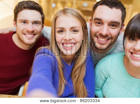 people, leisure, friendship and technology concept - group of smiling friends taking selfie