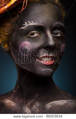 Black painted woman with body art and face art.